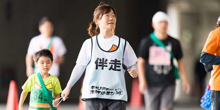 紐を持って走る子供ランナーと伴走の母親