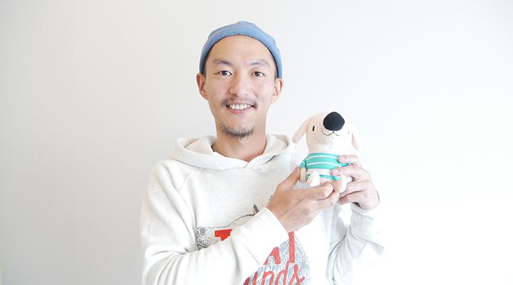 エルくんのマスコットを手に笑顔の西田さん