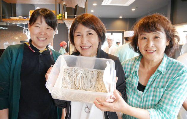 切った蕎麦を持って笑顔の参加者
