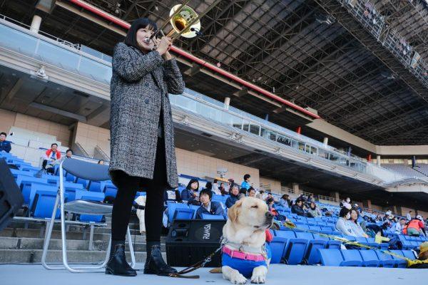 トロンボーンを演奏する女性。足元に盲導犬