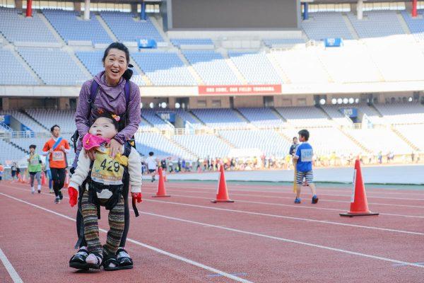 母に支えられ自分の足で歩く障がいのある女の子