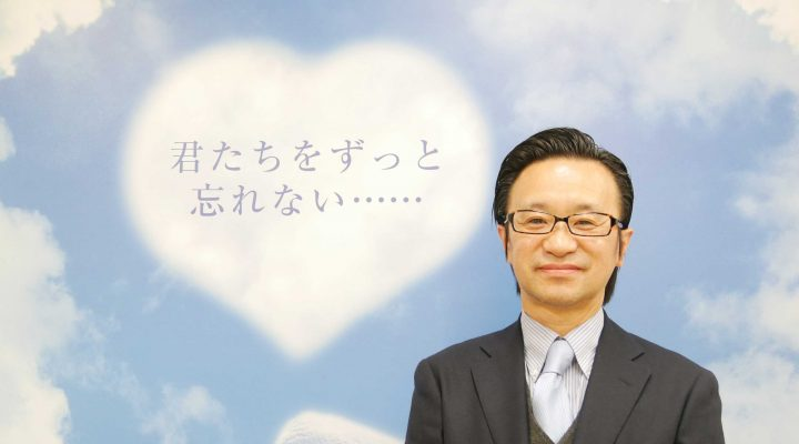 会社のタペストリーの前で笑顔の若月社長の写真