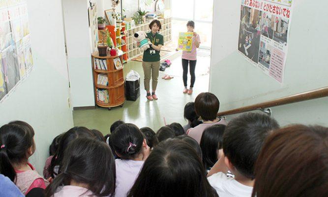 エルくんぬいぐるみを持って説明するスタッフの写真。園児たちは静かに聞いている