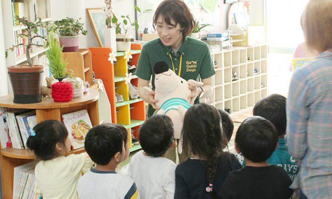 子どもたちにエルくんを渡すスタッフの写真