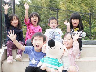 エルくんを持って、笑顔の子どもたちの写真