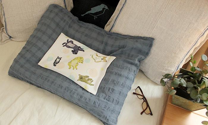 白い生地に犬が沢山書かれたイラストの枕がベッドに置かれている