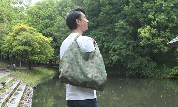 男性がエコバッグを肩からかけている。グリーンがメインのカモフラ柄
