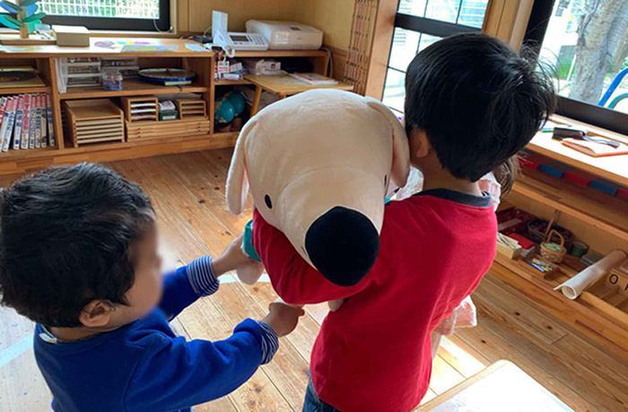 BIGエルくんを抱きしめる子どもたちの後ろ姿。